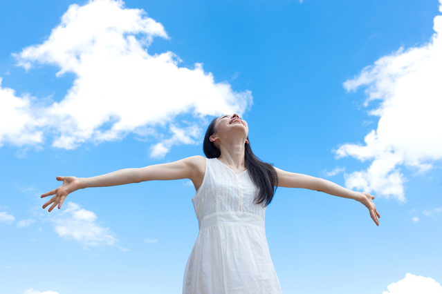 空をバックに深呼吸する女性